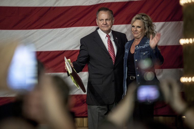 Image: Moore stands with his wife Kayla at a campaign rally.
