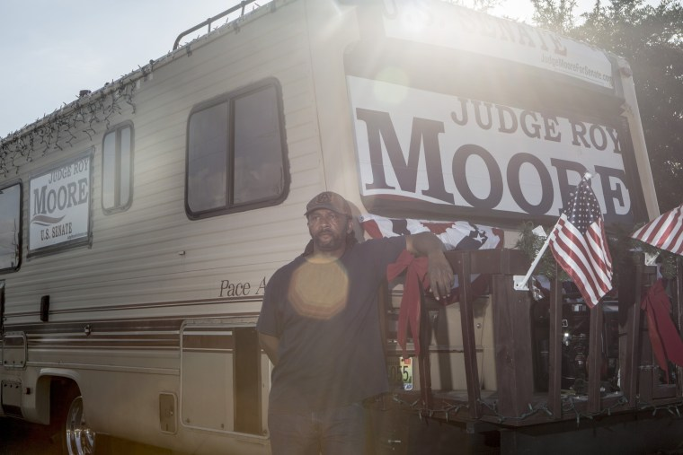 Image: Romeo Ryan stands for a portrait with his RV while stopped along the side of the road in Daphne, Alabama on his way to the Moore rally in Fairhope.