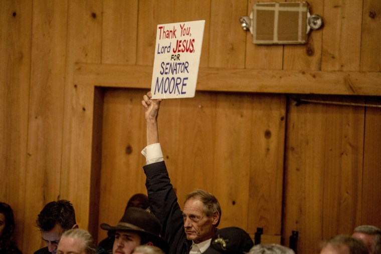 Image: A Roy Moore supporter holds up a sign at the campaign rally.