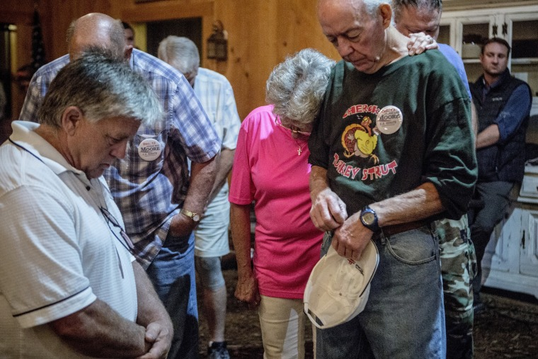 Image: Moore supporters bow their head in prayer.