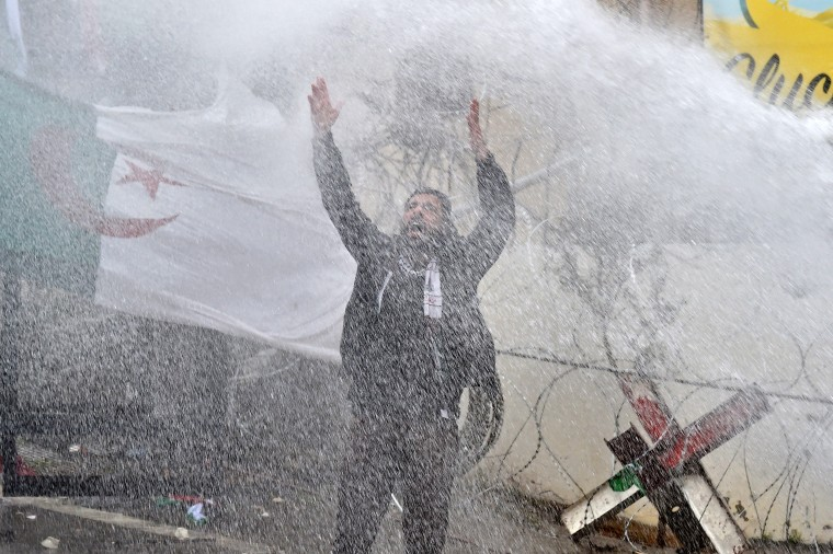 Image: A man shouts as he stands in front of water cannon used by Lebanese riot policemen to disperse protesters during a protest