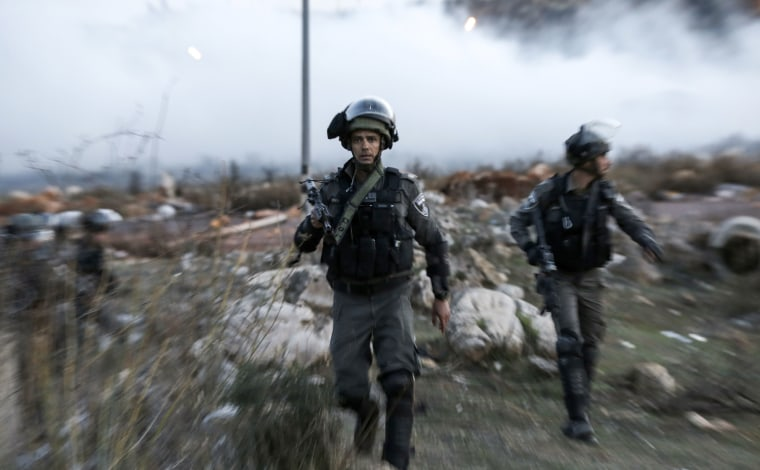 Image: An Israeli border policeman looks on as he walks through tear gas fumes during clashes with Palestinian protesters