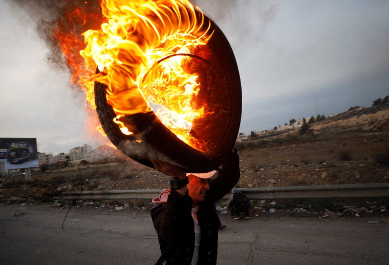 Image: A Palestinian holds a burning tire during clashes with Israeli troops near the Jewish settlement of Beit El, near Ramallah