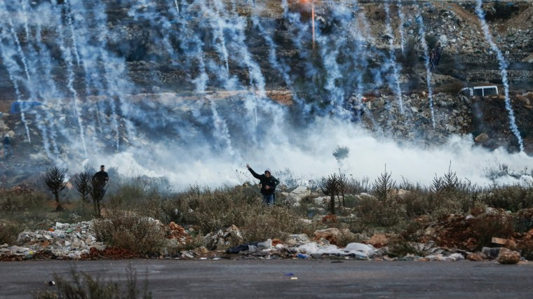 Image: Palestinian protesters run from falling tear gas canisters fired by Israeli forces