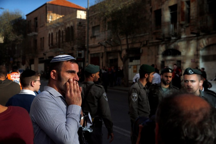 Image: An onlooker reacts near the area where police said a Palestinian stabbed an Israeli security guard at the main bus station in Jerusalem