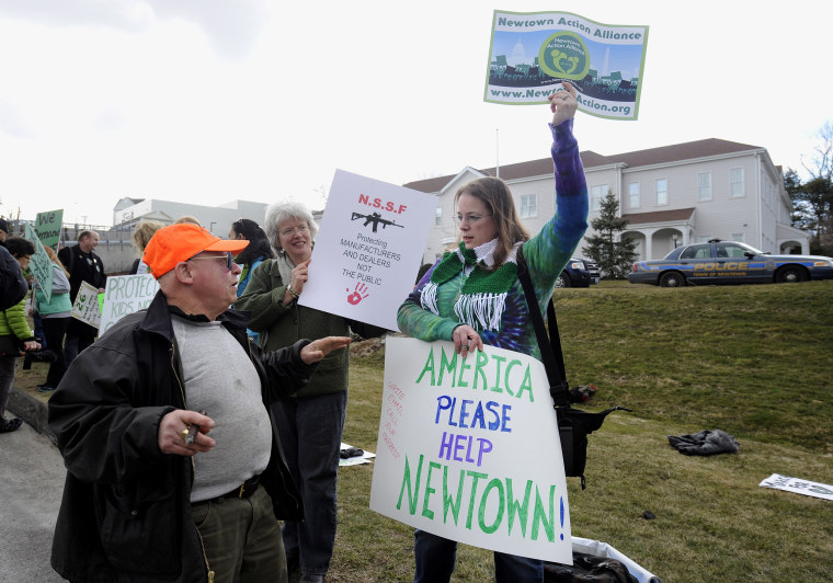 Image: Phillip W. Mauriello of Watertown, Connecticut, left, who is not in favor of any changes to gun laws in Connecticut speaks with Erin Nikitchyuk of Sandy Hook