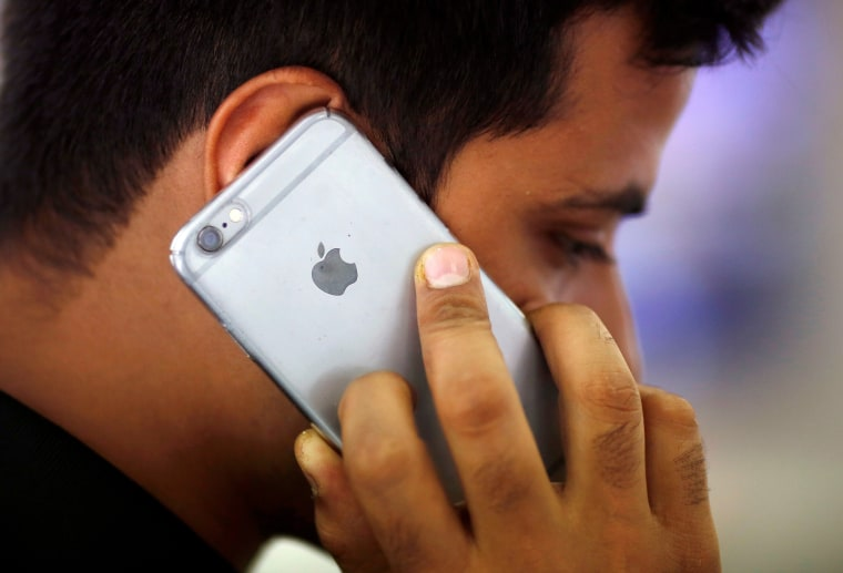 Image: FILE PHOTO: A man talks on his iPhone at a mobile phone store in New Delhi