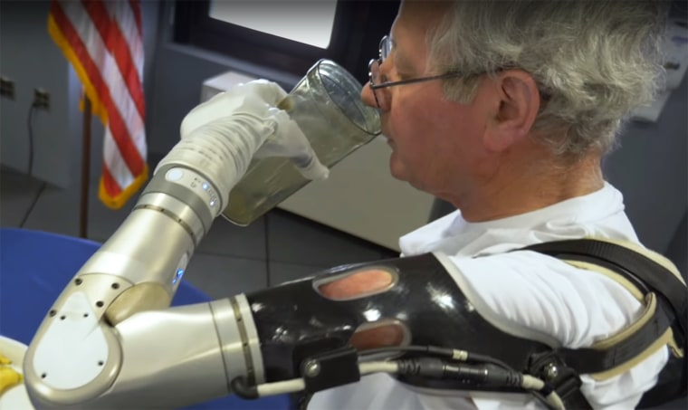 Image: A veteran drinks a glass of water with DARPA's LUKE Arm