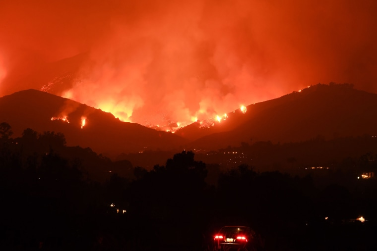 Image: A man sits in his car as he watches flames from the Thomas Fire in the hills of Montecito