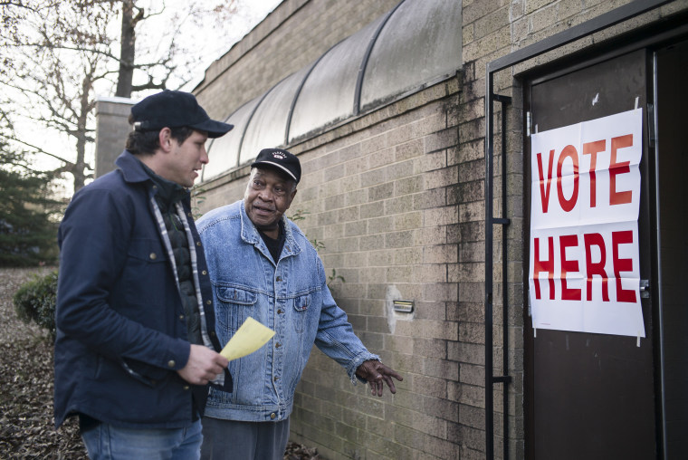 Image: People great each other outside a polling station at the Norwood Community Center in Birmingham, Ala.