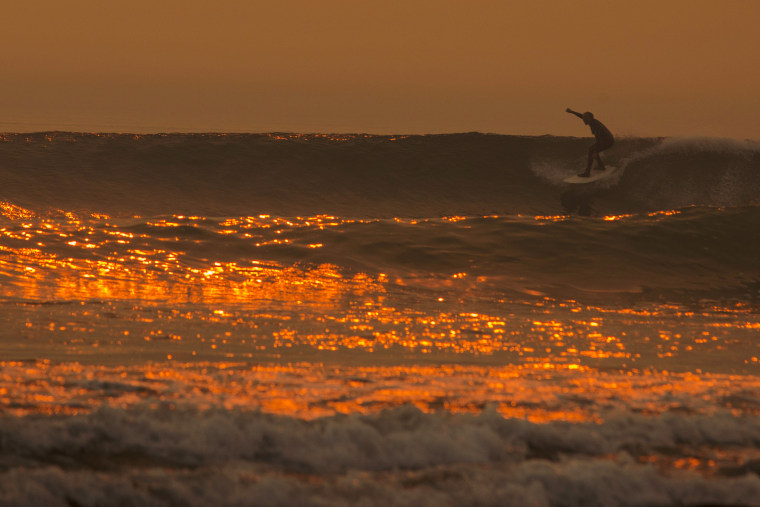 Image: A smoke-filled sky filters orange light around a surfer