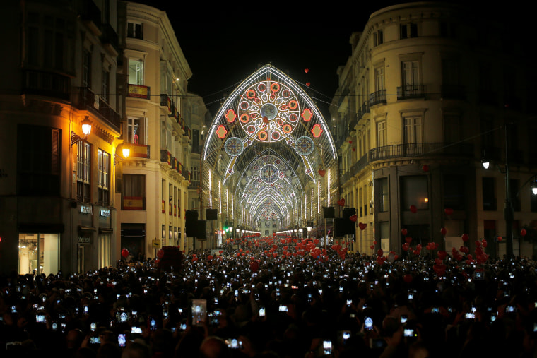 Image: People use mobile phones to take pictures as Christmas lights are turned on to mark the start of the Christmas season in downtown Malaga