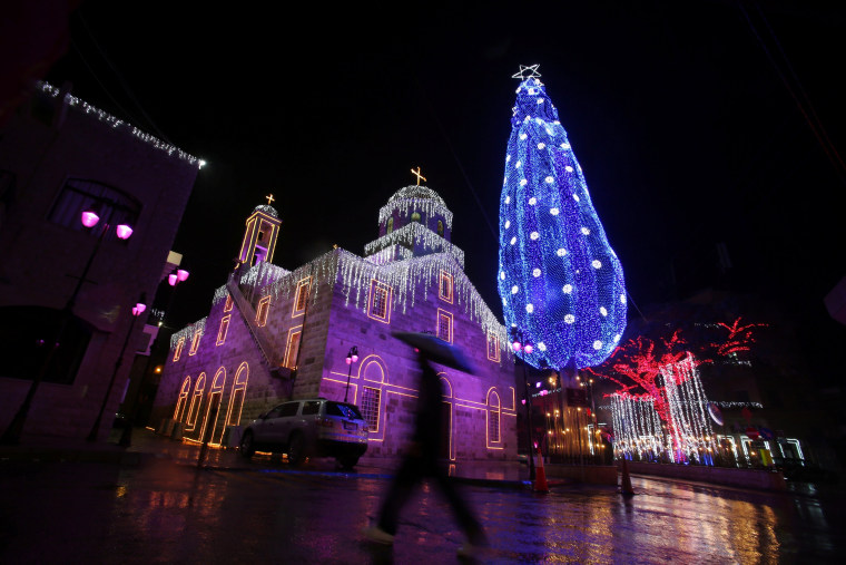 Image: A man walks past Christmas decorations in Maghdouche village near Sidon, Lebanon