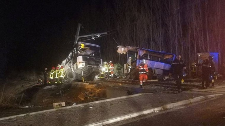 Image: Rescue workers are seen on the site of collision between train and school bus in Millas