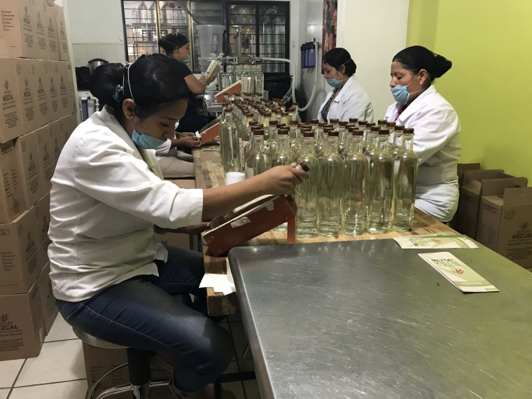 Employees bottle the mezcal in the company's warehouse in Oaxaca and apply the labels by hand. As an employee of Koch el Mezcal, they receive free english classes.