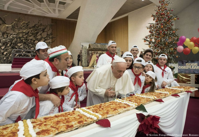 "Image: Pope Francis blows out a candle on a pizza on Dec. 17, 2017 during an audience with children assisted by ""Dispensario Santa Marta"", a Vatican pediatric clinic at the Vatican. Pope Francis is celebrating his 81st birthday."