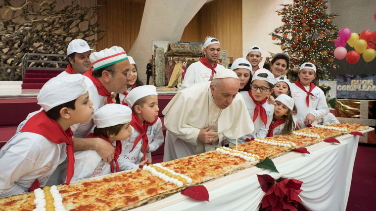 Image: Pope Francis blows on a cake to celebrate his birthday during a special meeting at Paul VI hall at the Vatican