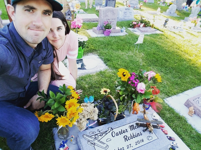 Brandon and Caitlin Robbins visit the grave site of their son Carter, who was stillborn in 2016.