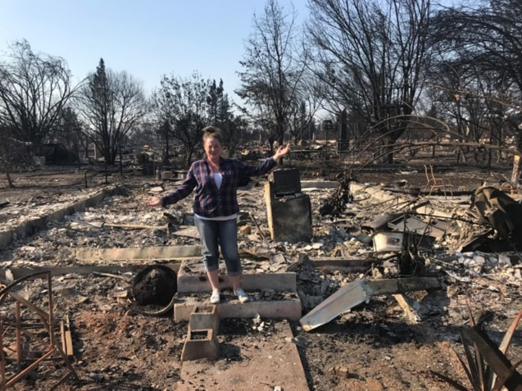 Lilly's mom, Jessica Biagini, stands among what's left after their home burned down in an October wildfire.