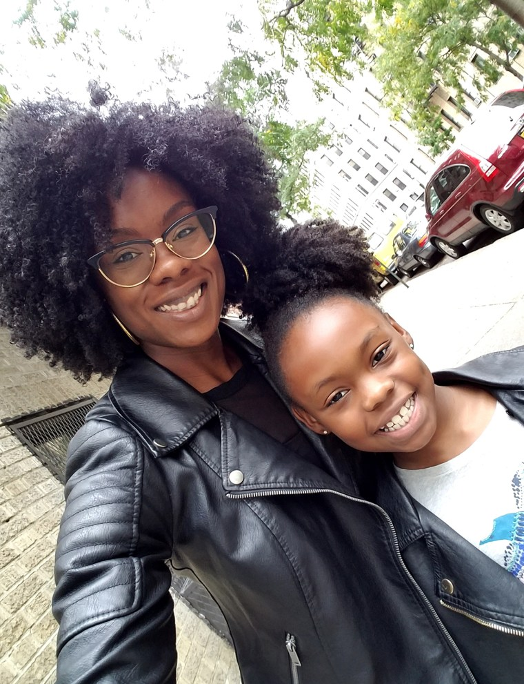 Charles poses with her daughter, who now loves to wear her hair curly just like her mom.