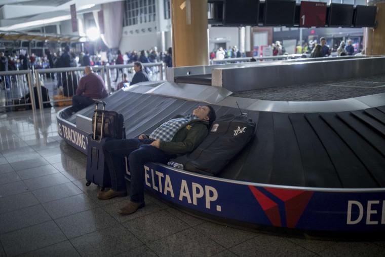 Image: A traveler sleeps on a baggage carousel at Hartfield-Jackson Atlanta International Airport, Dec. 17, 2017, in Atlanta.