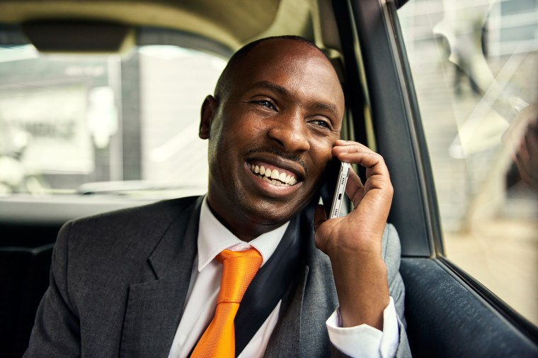 Medium close-up shot of an elegant male rider using a cell phone in a car