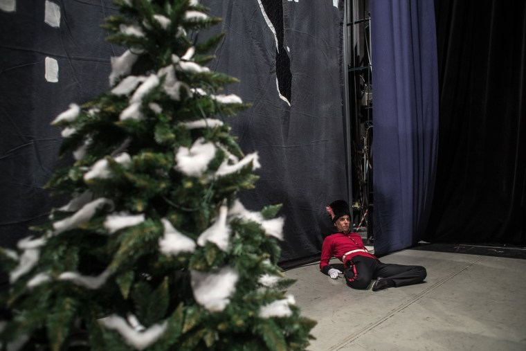 Image: A dancer from the Czech National Ballet stretches and warms up in a stage corner before a performance at the National Theatre in Prague on Dec. 16.