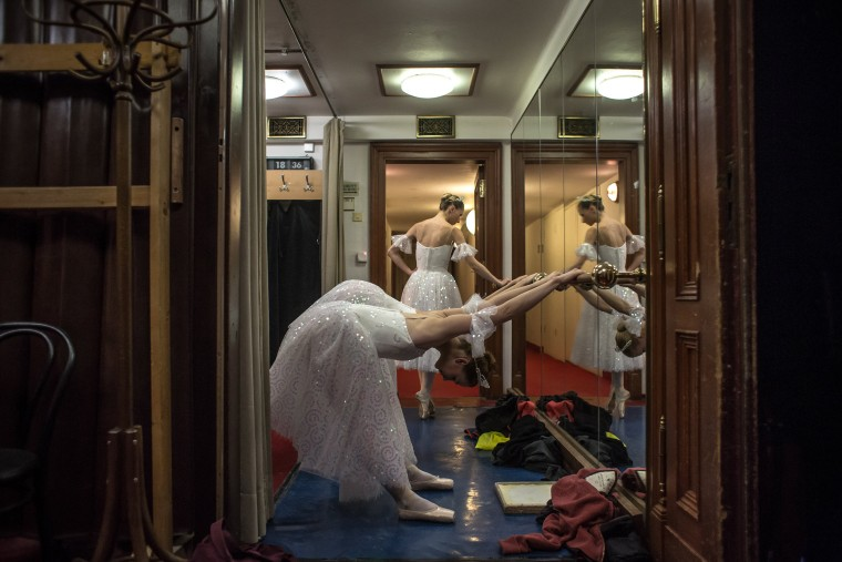 Image: Dancers warm up backstage while their fellow company members dance in Prague on Dec. 16.