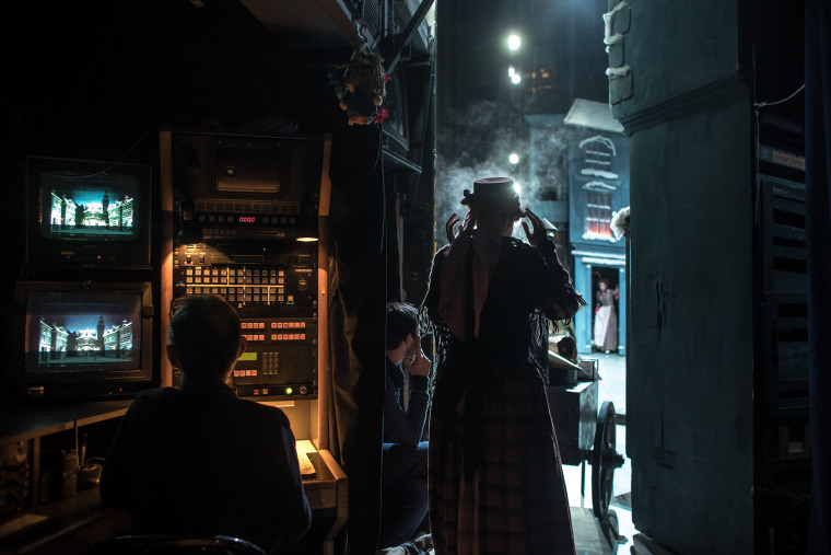 Image: Stage technicians look over the performance as a dancer waits in the wings to join the other dancers on stage in Prague on Dec. 16.