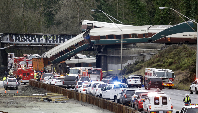 Image: Cars from an Amtrak train lay spilled onto Interstate 5