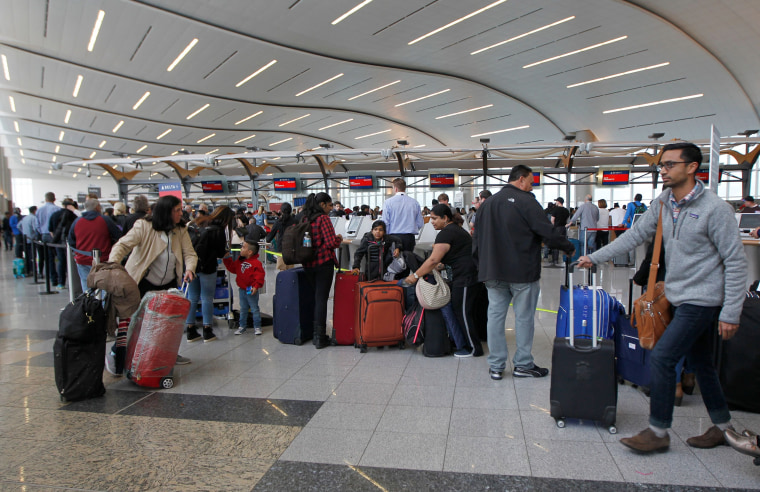 Image: Airline passengers arrive to stand in line at the Delta Airlines international counter