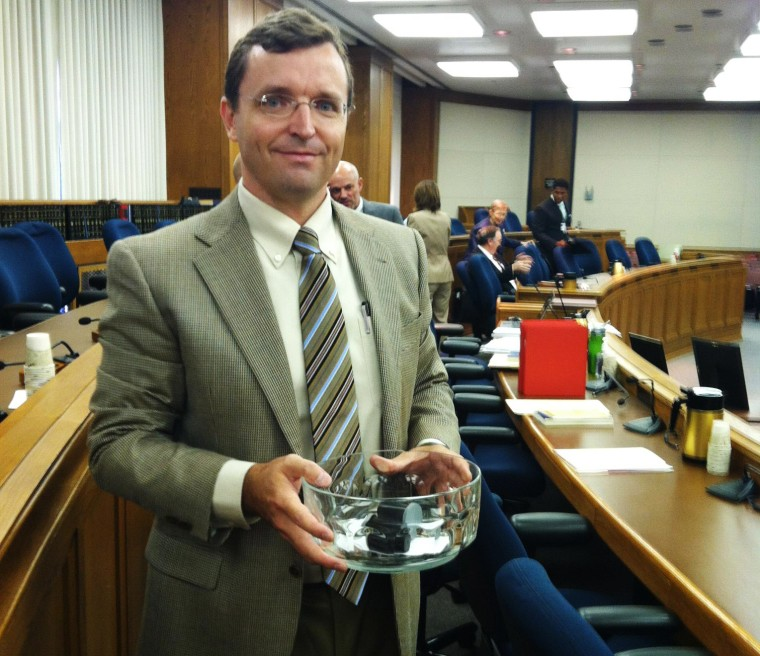 Matt Abell, Lead SBE Election Administration Analyst, holds the crystal bowl from which the political party slips were drawn at the June 26th board meeting.