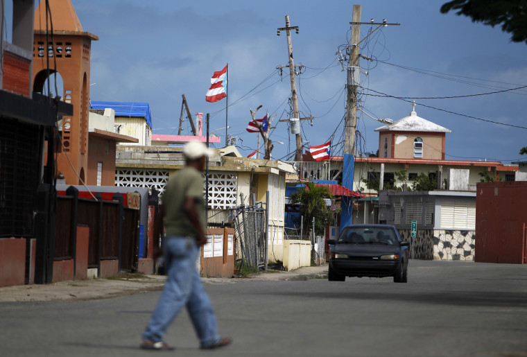 Image: A man crosses a street in the Punta Santiago beachfront neighborhood of Humacao