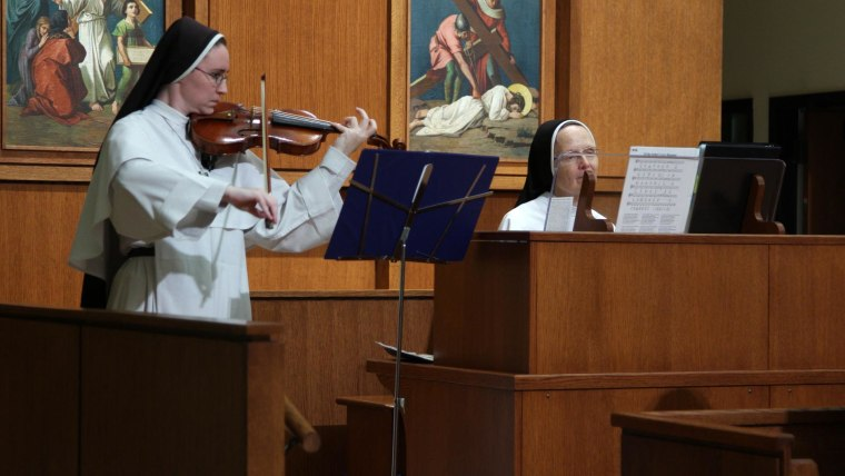 Sister Joseph Andrew Bogdanowicz accompanies a fellow violin playing sister (right) during vespers.