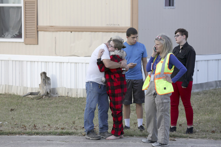 Image: Ron Lawrence, left, comforts his daughter Kallie Lawrence, 11, who knew the  boy that was killed in the shoot out between Bexar County Deputies and a wanted suspect woman in Pecan Grove Trailer Park in Schertz, Texas, on Dec. 21, 2017.