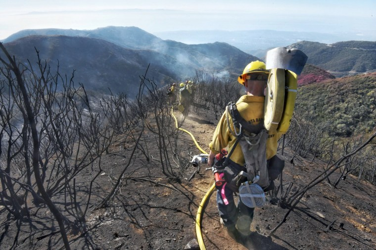 Image: Santa Barbara County Firefighters haul dozens of pounds of hose and equipment down steep terrain below E. Camino Cielo to root out and extinguish smoldering hot spots in Santa Barbara, California on Dec. 19, 2017.