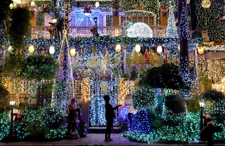 Image: A woman stands outside of a house lit up by christmas light installations in Rizal