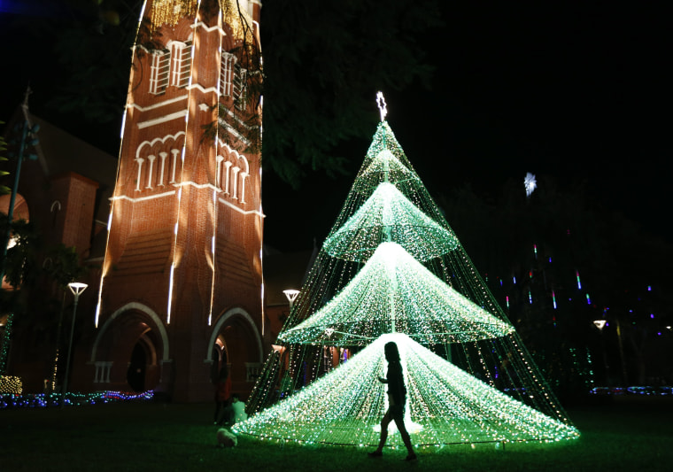 Image: A girl walks past a lit Christmas tree at Holy Trinity Cathedral in Yangon