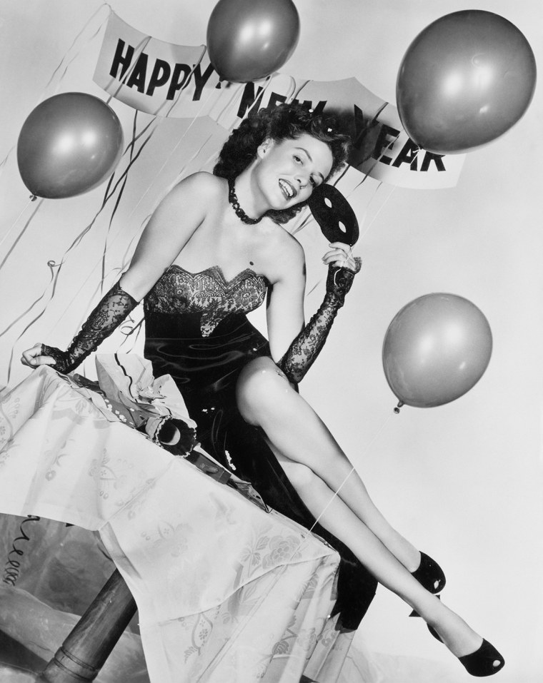 Young woman sitting on a table with balloons and sign (EV006209_H)