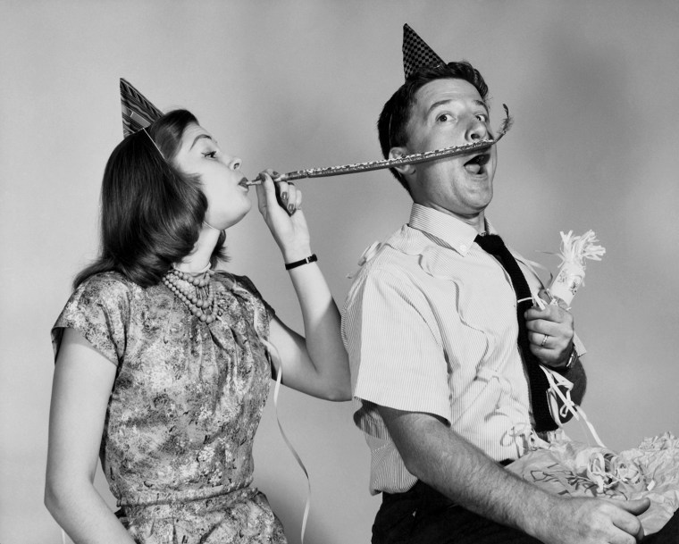 Young woman blowing a noisemaker near a young man's face. Photo by: Superstock/Everett Collection(255-28547)