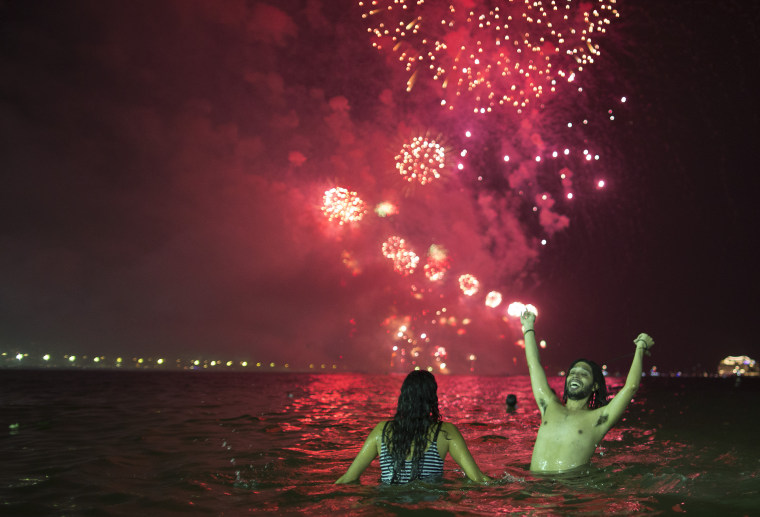 People watch the fireworks exploding over Copacabana beach during the New Year's Eve celebrations in Rio de Janeiro, Brazil, Sunday, Jan. 1, 2017.