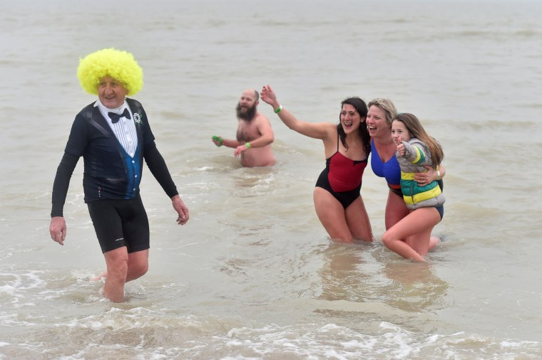 Image: Revellers take part in a New Year's dive in Ostend