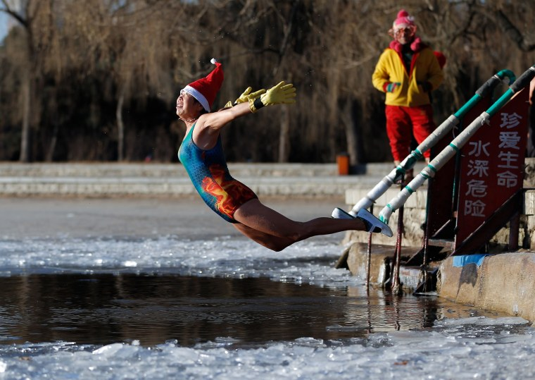 Image: A woman wearing a Santa hat dives into a partly frozen lake