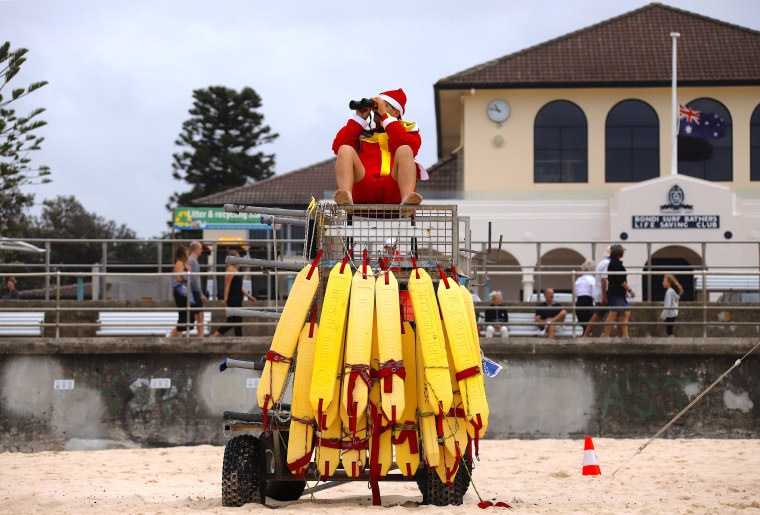 Image: A surf lifesaver wearing a Christmas hat uses binoculours to watch swimmers on Christmas Day at Sydney's Bondi Beach