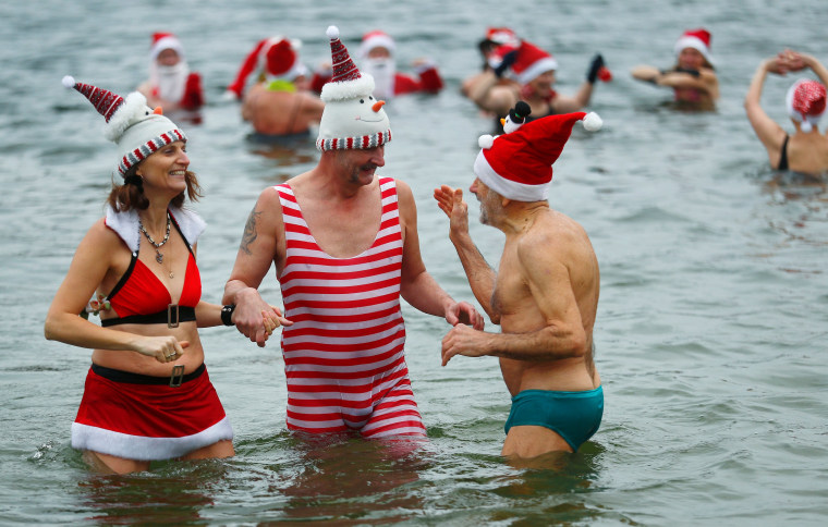 "Image: Members of ice swimming club ""Berliner Seehunde"" (Berlin Seals) take a dip in the Orankesee lake in Berlin as part of their traditional Christmas ice swimming session, in Berlin"