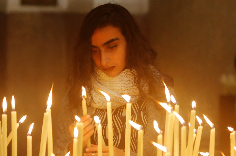 Image: An Egyptian woman lights a candle during a mass on Christmas Eve