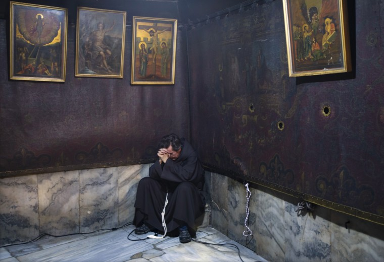Image: A Franciscan monk prays in the grotto of the Church of Nativity