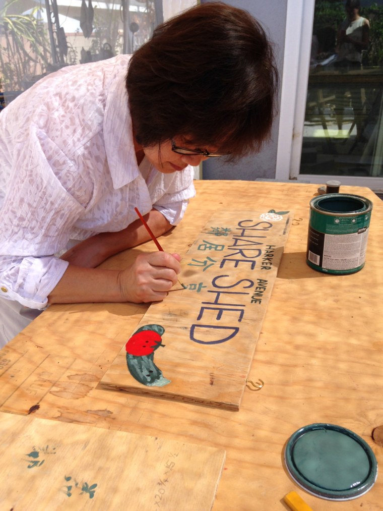 Jenny Lee, one of Wen Lee's neighbors in Temple City writes Chinese on the Share Shed sign.