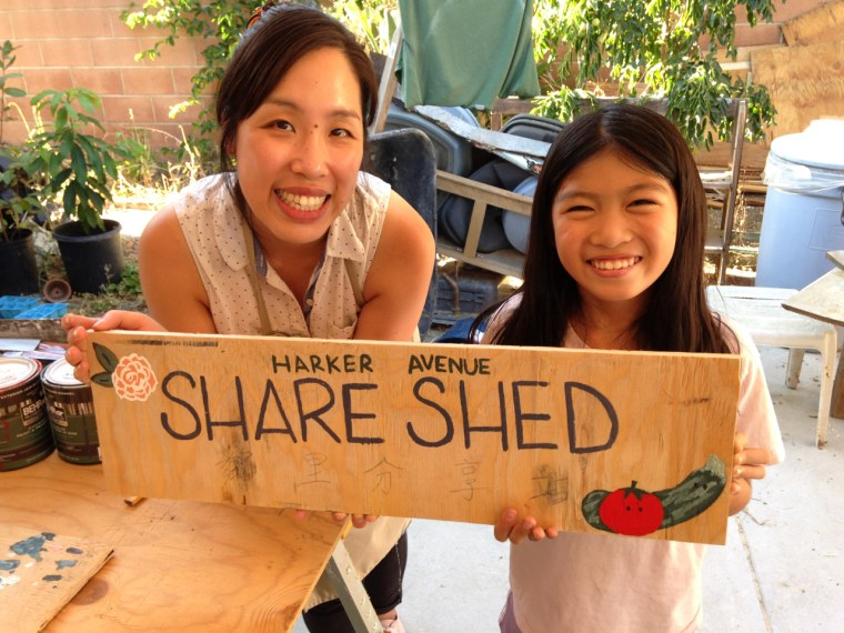 Jessica Lee and Priscilla Seto show off their contributions to the Share Shed sign.