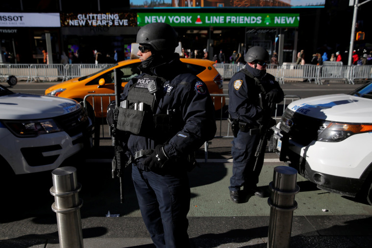 Image: New York Police Department Strategic Response Group members stand in Times Square to provide security ahead of New Year's Eve celebrations in Manhattan